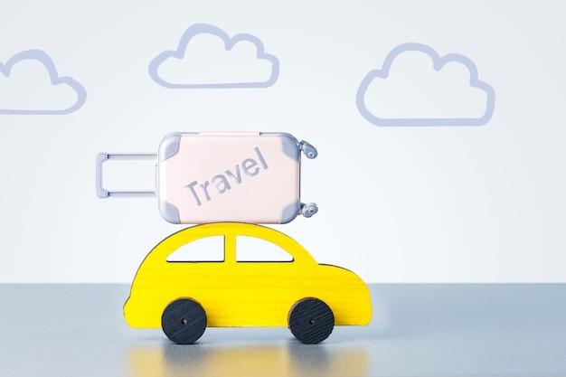 노란색 장난감 자동차 지붕에 가방입니다. 관광, 휴가, 여행 개념입니다.