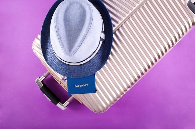 スーツケース、パスポート、紫色の背景の帽子「旅行」と休日の概念