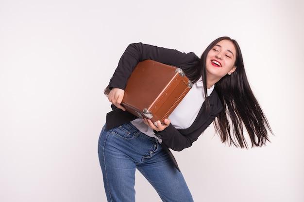 スーツケース、旅行、人々のコンセプト。白で古い茶色のスーツケースを保持しているアジアの女性