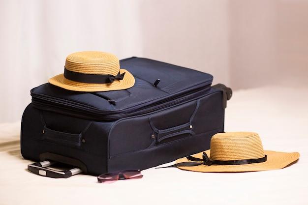 スーツケースのトラベルバッグと麦わら帽子は、ホテルの送迎と海の休憩所への旅行でホテルの部屋のチェックインのベッドに横たわっています