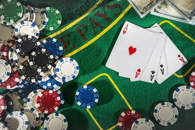 緑のポーカーテーブルにドル、トランプ、ポーカーチップが入ったスーツケース。