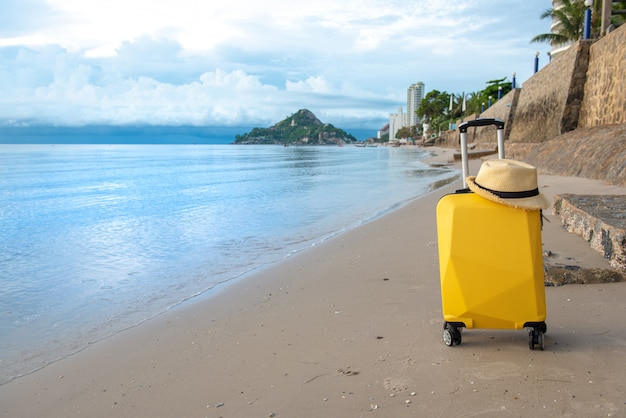 Suitcase with hat on the beach with clouds blue sky, travelling concept.