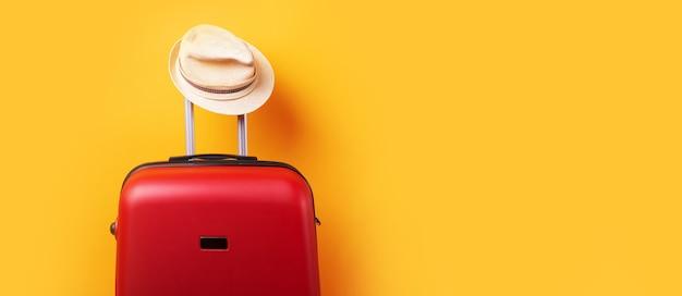 黄色の背景の上の帽子とスーツケース最小限の創造的な旅行の概念