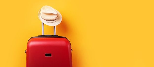 Suitcase with hat over yellow background minimal creative travel concept