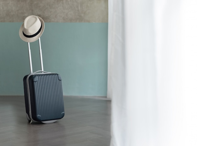 Suitcase with male hat on pastel blue and bare wall.