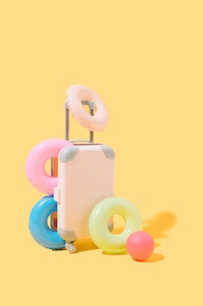 Suitcase with many floats and a ball on a yellow background travel and summer 3d illustration