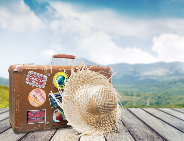背景に麦わら帽子とスーツケース