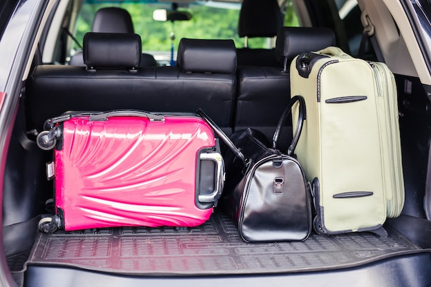 休暇に向けて出発する準備ができているスーツケースと車のトランクのバッグ