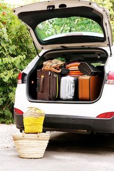 休日に出発する準備ができている車のトランクのスーツケースとバッグ