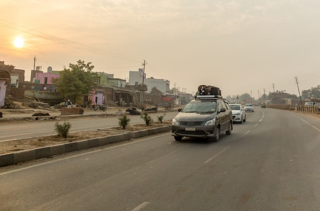 Suitcases tied to the roof of the car while driving on the road in india on vacation.