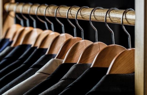 ラックにぶら下がっている男性用のスーツ。衣料品小売店のハンガーにぶら下がっているさまざまな色のメンズスーツ、クローズアップ。メンズシャツ、スーツはラックにぶら下がっています。ブティックでジャケットを着たハンガー。