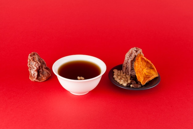 Sujeonggwa - korean cold fruit tea or chilled punch red background with copy space.