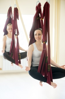 Sukhasana yoga pose in hammocks