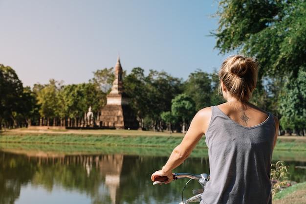 Молодая белокурая женщина ехать велосипед смотря архитектуру в природе, в sukhotai таиланде