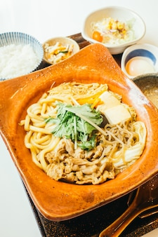 Suki noodles in hot plate with rice