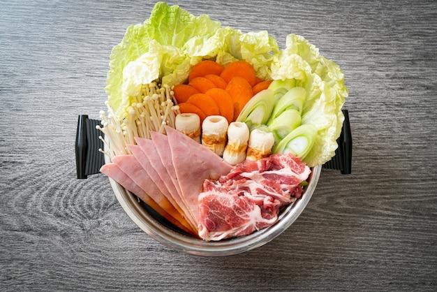 Черный суп сукияки или сябу в горячем горшочке с сырым и овощным мясом - стиль японской кухни