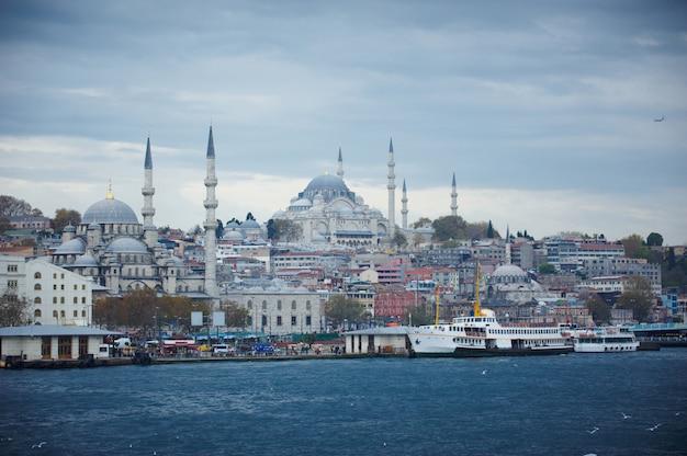 Городской пейзаж стамбула с шлюпками и мечетью suleymaniye, турцией.