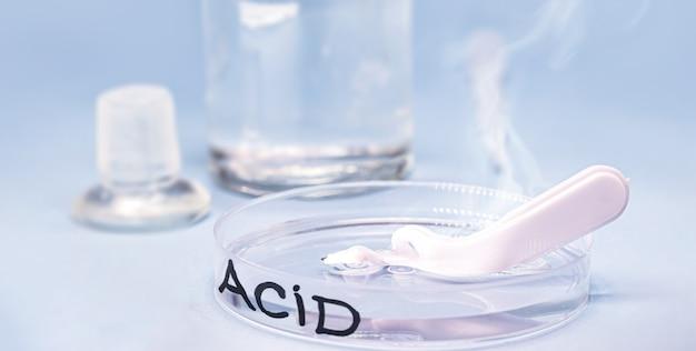 Серная кислота в чашке петри, плавильная пластиковая ложка, коррозионная кислота в действии