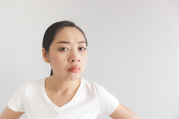 Sulk and grumpy face expression of woman in white t-shirt. concept of offended peevish and sulky.
