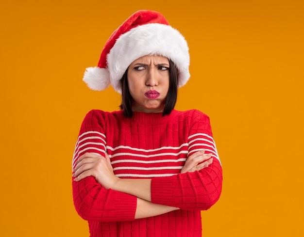 복사 공간 오렌지 벽에 고립 된 측면 퍼핑 뺨을보고 닫힌 자세로 서 산타 모자를 쓰고 찡그린 어린 소녀