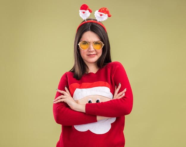 복사 공간 올리브 녹색 배경에 고립 된 측면을보고 닫힌 자세로 서 안경 산타 클로스 스웨터와 머리띠를 입고 찡그린 젊은 예쁜 백인 여자