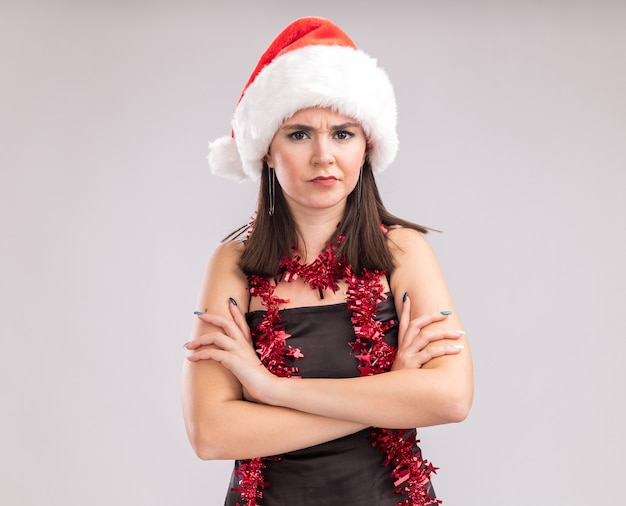 Sulking young pretty caucasian girl wearing santa hat and tinsel garland around neck standing with closed posture looking at camera isolated on white background