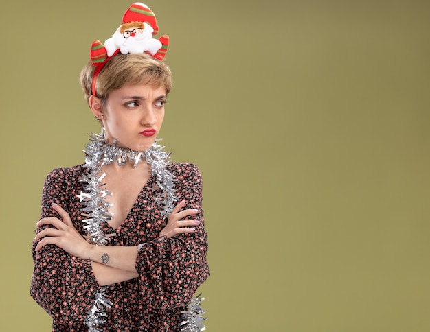 Sulking young pretty girl wearing santa claus headband and tinsel garland around neck standing with closed posture looking at side isolated on olive green wall with copy space