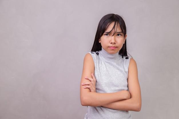 팔을 가진 음산한 일본 아이는 회색 배경에 건넜다.