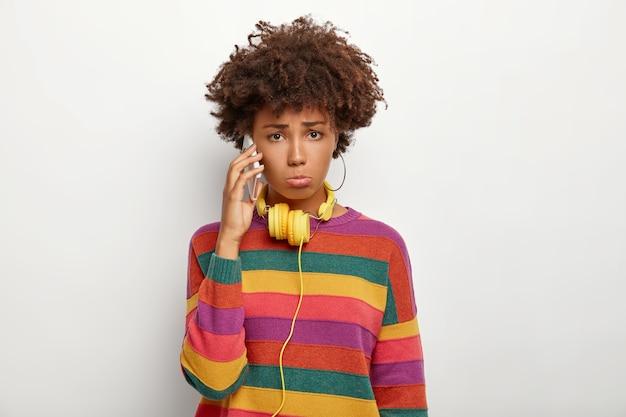 Угрюмая недовольная афроамериканка ведет неприятный разговор через смартфон, носит красочный повседневный полосатый джемпер, использует желтые наушники, чем-то недовольна