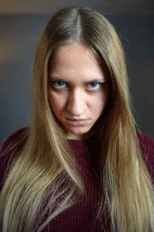 Sullen look from under eyebrows on  angry face of long-haired caucasian girl, dark blue wall.