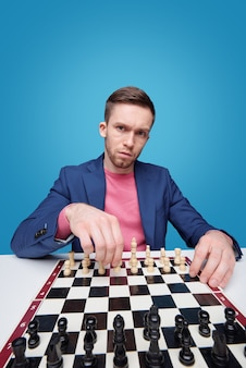 Угрюмый молодой человек смотрит на вас, сидя у шахматной доски и играя в одиночестве