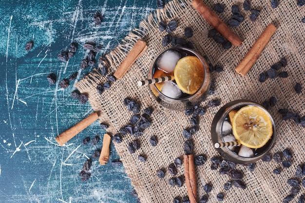 Sultana, lemonnd cinnamons con una tazza di bevanda sul blu.