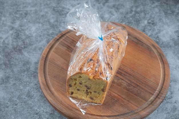 Султанский пирог, обернутый стрейч-пленкой на деревянной доске.