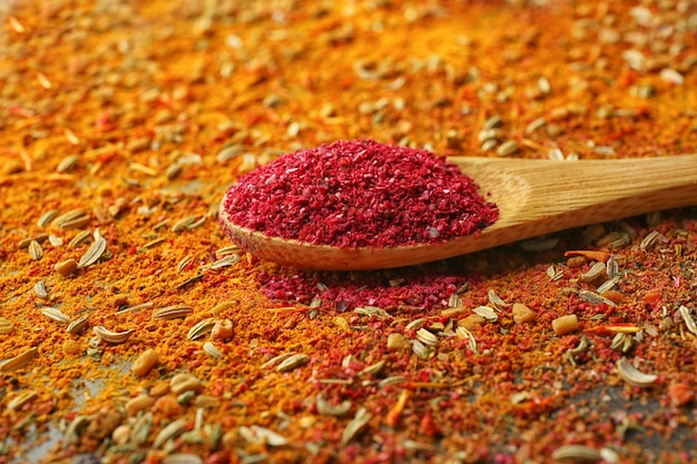 Sumac in wooden spoon on mixed spices