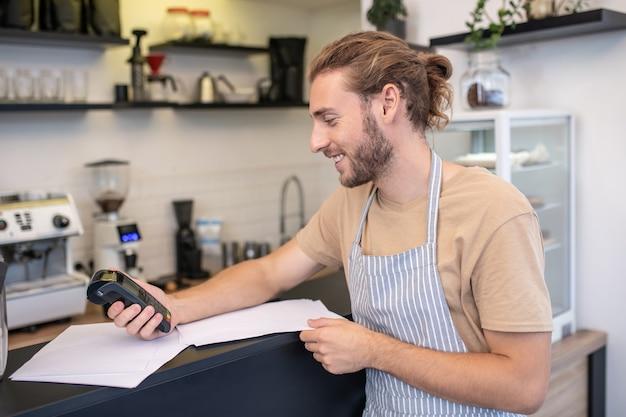 요약. 카페에서 청구서를 확인하는 프로필에 앞치마에 젊은 성인 장발 남자 미소