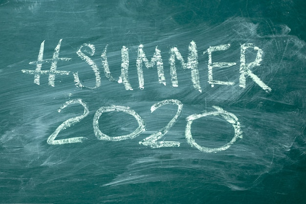 Summer 2020 hashtag it handwritten with white chalk on a green blackboard.