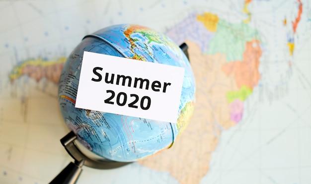 2020年夏のツアー-アトラスマップの背景に対して手に白いシート上のテキスト