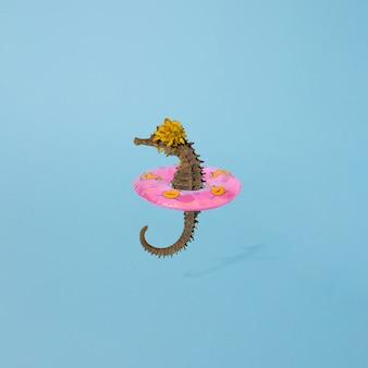 Лето 2021 года, морской конек с розовой пляжной резиной с желтыми утками. синий фон. креативная минимальная концепция.