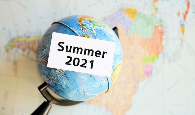 2021年夏-アトラスマップの背景に手に白いシート上のテキスト