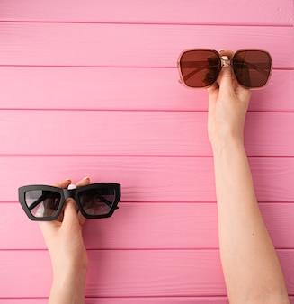 夏の抽象的な背景女性の手はファッショナブルなカップルのサングラスを保持します
