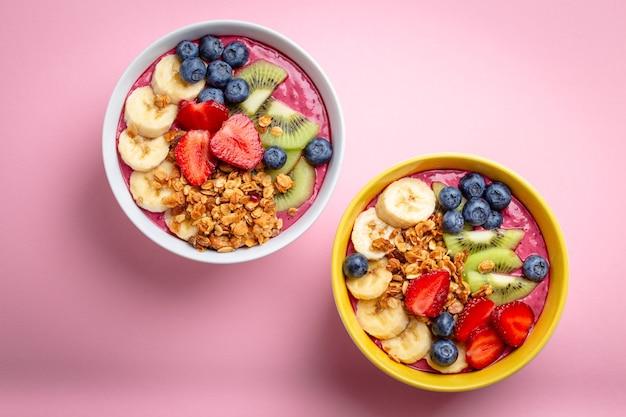 파스텔 핑크색 배경에 딸기, 바나나, 블루베리, 키위 과일, 그래놀라를 넣은 여름 아사이 스무디 그릇. 과일과 시리얼이 포함된 조식 그릇, 클로즈업, 위쪽 전망, 건강식