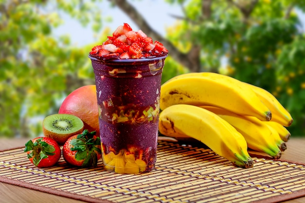 Summer acai smoothie with topping strawberries, banana, kiwi fruit and granola