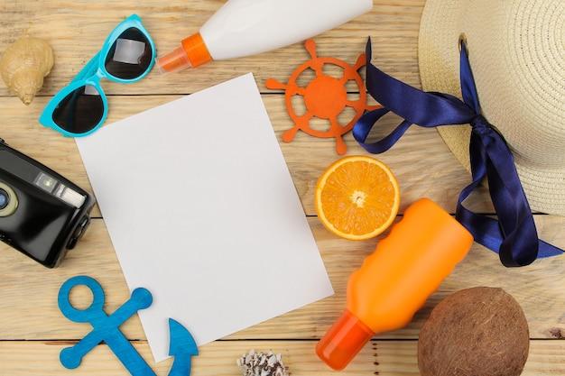 夏のアクセサリー。ビーチアクセサリー。帽子、日焼け止め、サングラス、カメラ、オレンジ色の自然な木のテーブル。上面図。