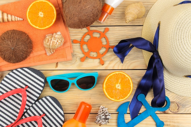 夏のアクセサリー。ビーチ アクセサリー。帽子、日焼け止め、サングラス、ビーチサンダル、オレンジ色の自然な木のテーブル。上面図。