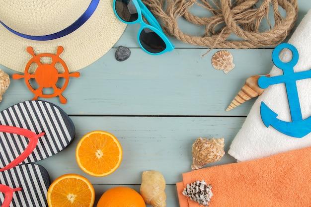 夏のアクセサリー。ビーチ アクセサリー。青い木製のテーブルにスリッパ、帽子、貝殻、タオル、サングラス。上面図。
