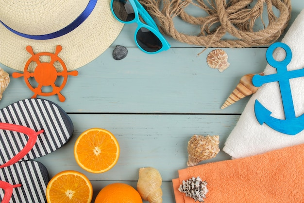 Summer accessories. beach accessories. slippers, hat, shells, towel, and sunglasses on a blue wooden table. top view.