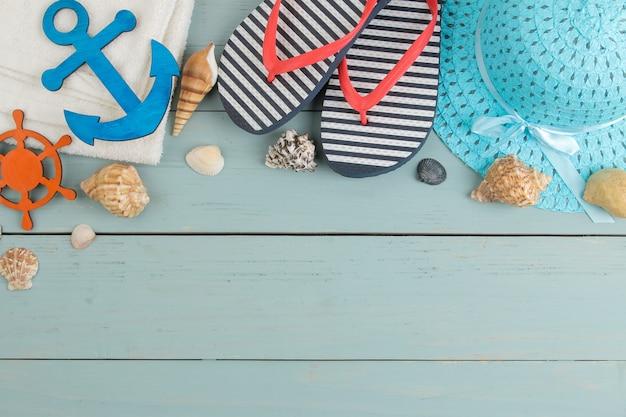 夏のアクセサリー。ビーチアクセサリー。青い木製のテーブルにスパンキング、帽子、貝殻、タオル。上面図。