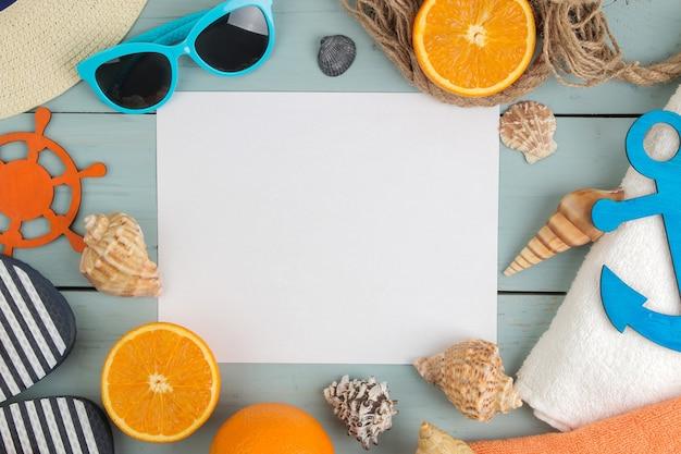夏のアクセサリー。ビーチアクセサリー。青い木製のテーブルにスパンキング、帽子、貝殻、タオル、サングラス。上面図。