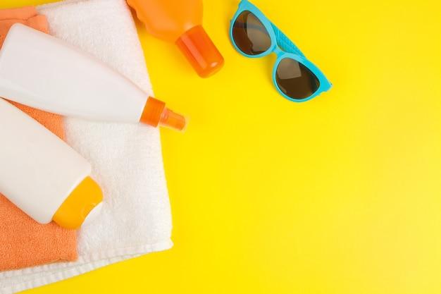 夏のアクセサリー。ビーチアクセサリー。明るい黄色の背景に日焼け止めとタオル。上面図。