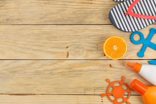 夏のアクセサリー。ビーチアクセサリー。自然な木製のテーブルに日焼け止め、ビーチサンダル、オレンジ。上面図。